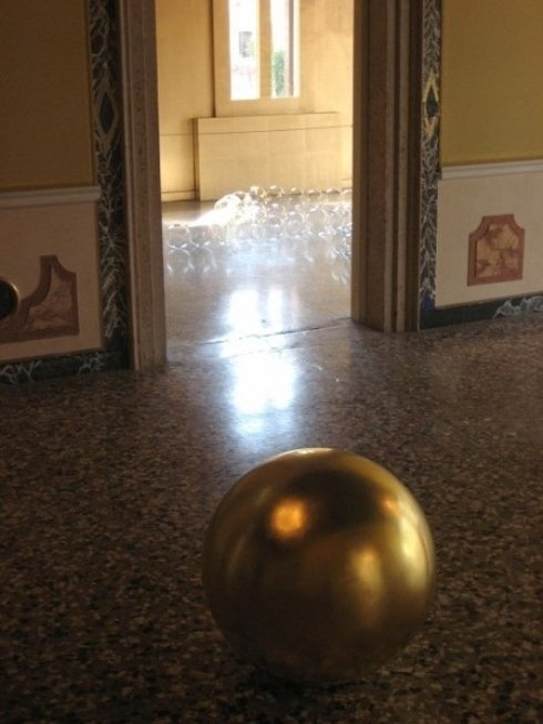 una sfera dorata di james lee byars esposta nel palazzo