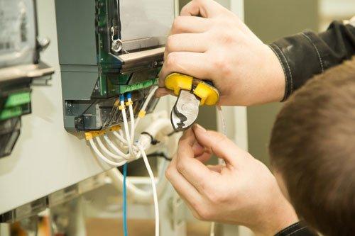 un uomo sta spellando dei cav con una pinza vicino a un quadro elettrico