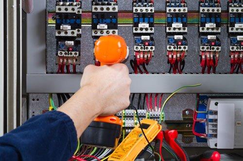 una mano con un trapano avvitatore arancione sta avvitando delle viti di un quadro elettrico. Sotto c'e' un tester di color giallo e accanto diversi contatori della luce