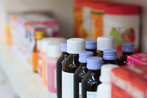 primo piano di uno scaffale con bottiglie di medicinali