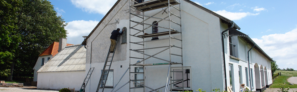 man paints the house white