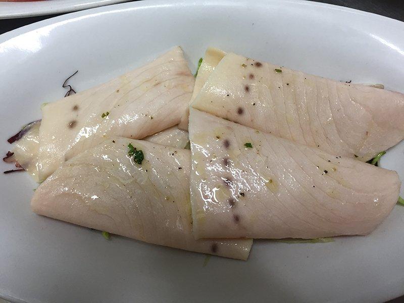delle fette di carpaccio di pesce spada in un piatto
