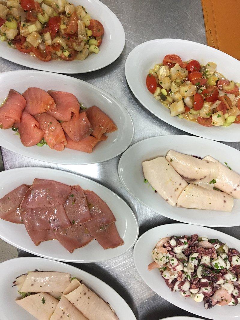 dei piatti con verdure tiepide,carpacci di salmone, pesce spada,polipo e altri tipi