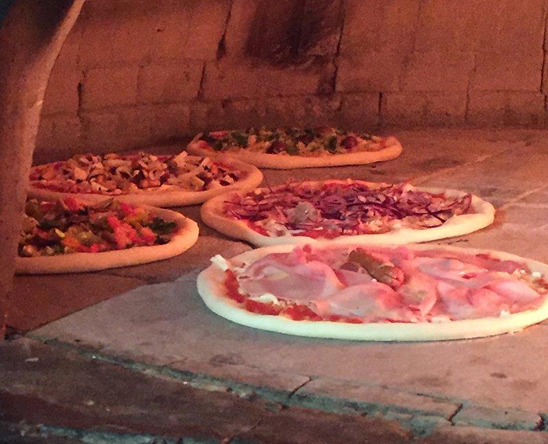 delle pizze di diversi gusti dentro a un forno a legna