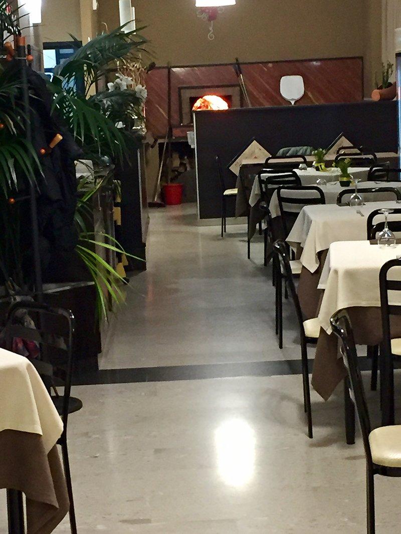 la sala del ristorante con dei tavoli e sulla sinistra delle piante