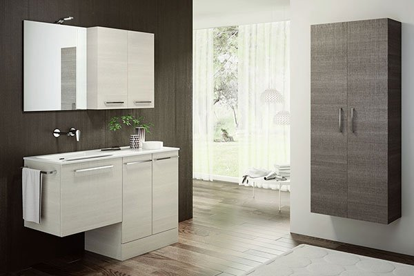un lavabo con mobili da bagno di color bianco e sulla destra un altro armadio di color marrone