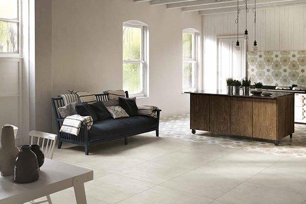 un divano in legno e sulla destra una penisola di una cucina