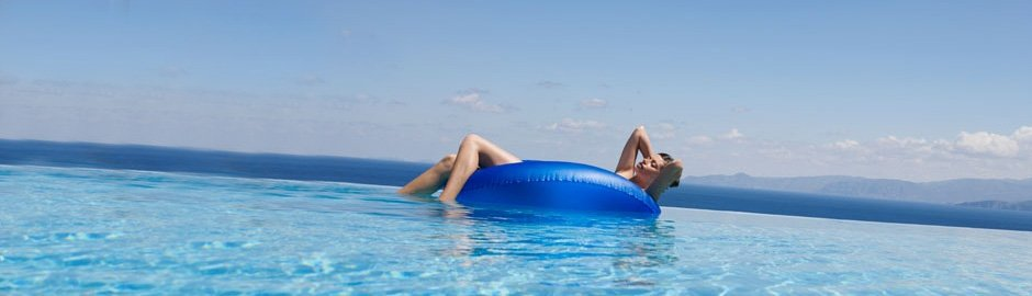 Lady floating in swimming pool on rubber ring