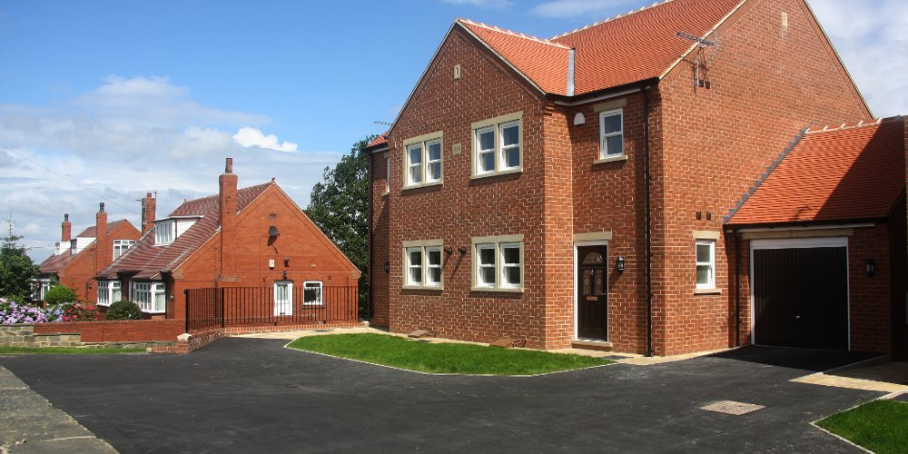 A large, detatched red brick house with garage and freshly tarmaced driveway