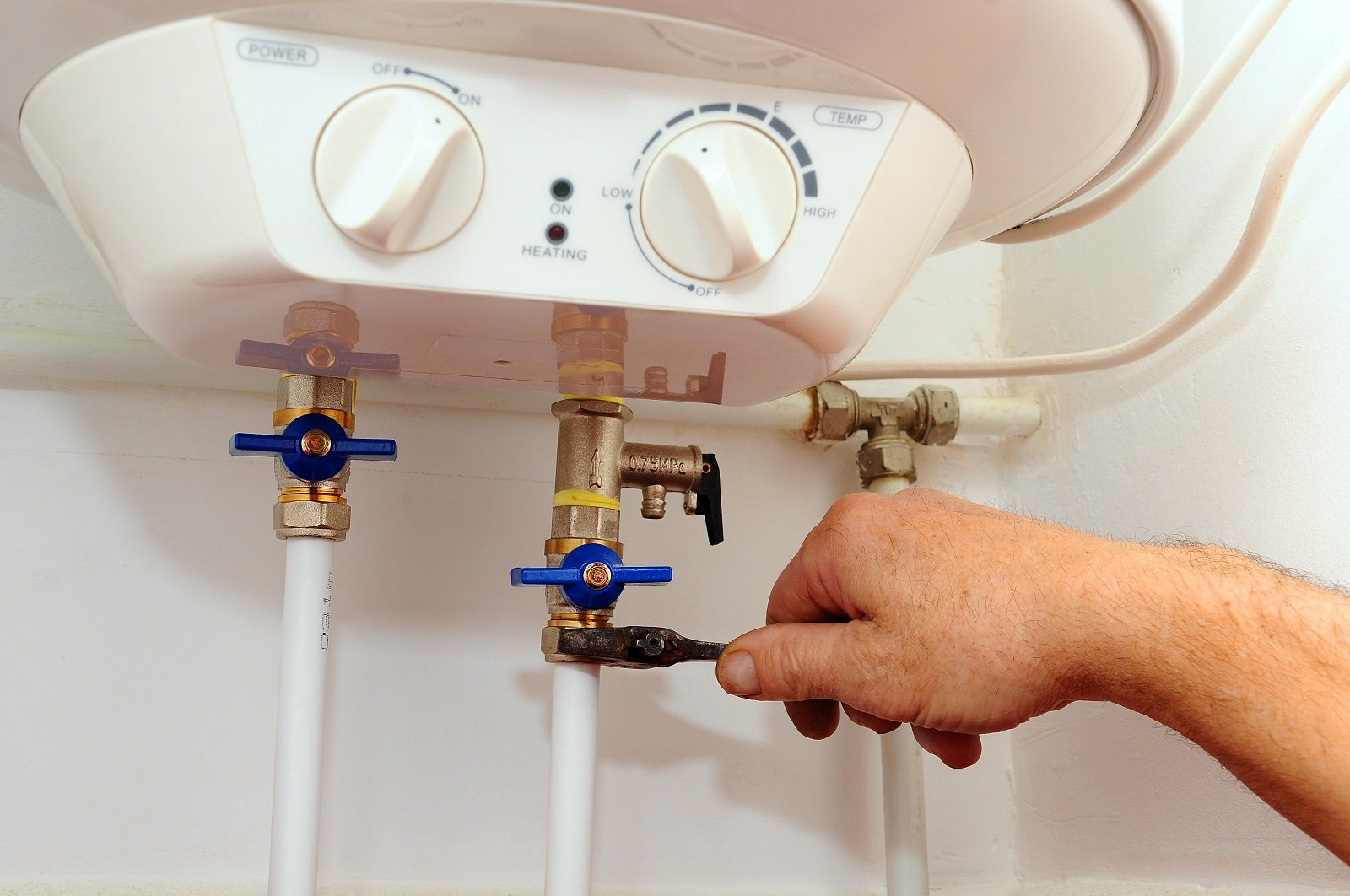 una mano appoggiata alla manopola del gas di una caldaia