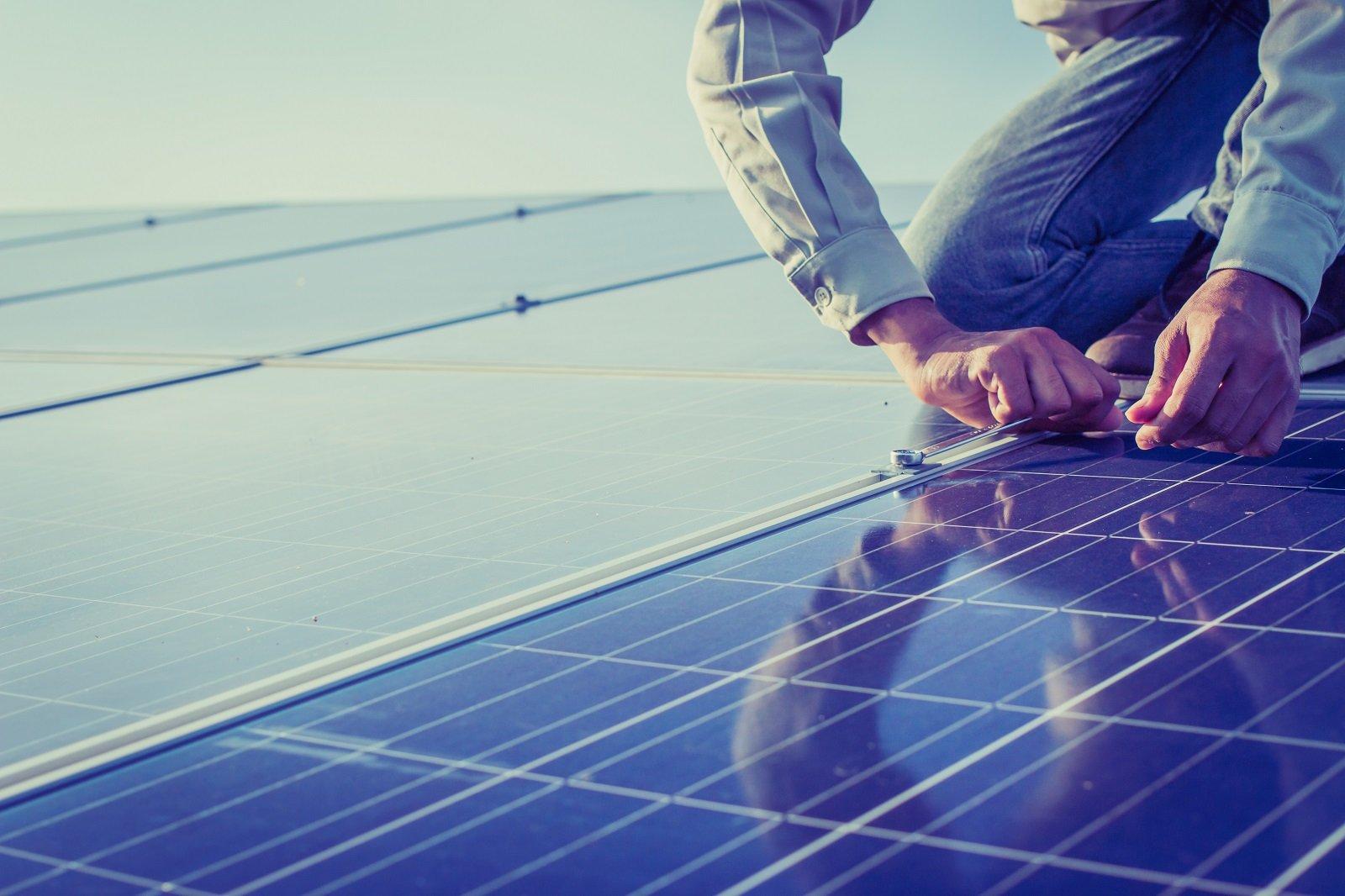 due mani che montano dei pannelli solari su un tetto