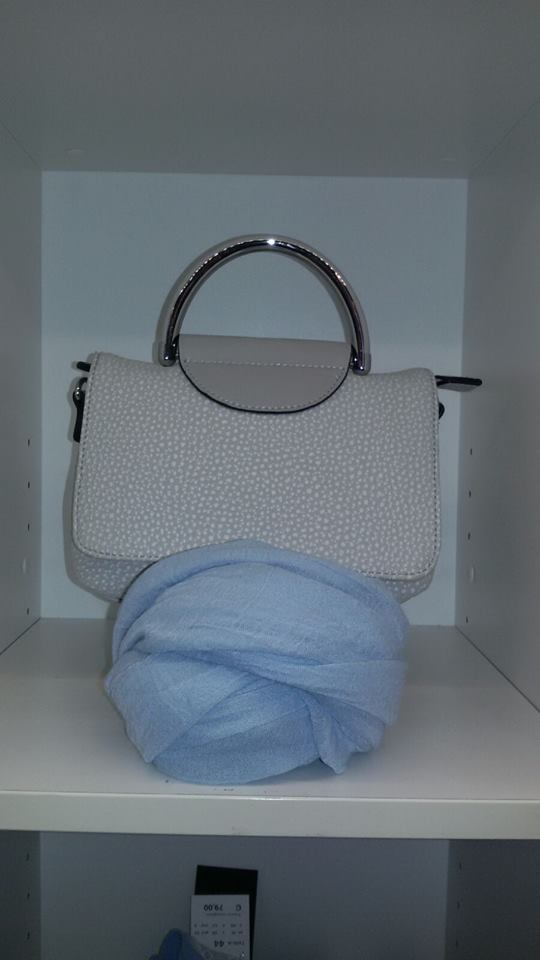 borsa da donna e foulard su una mensola