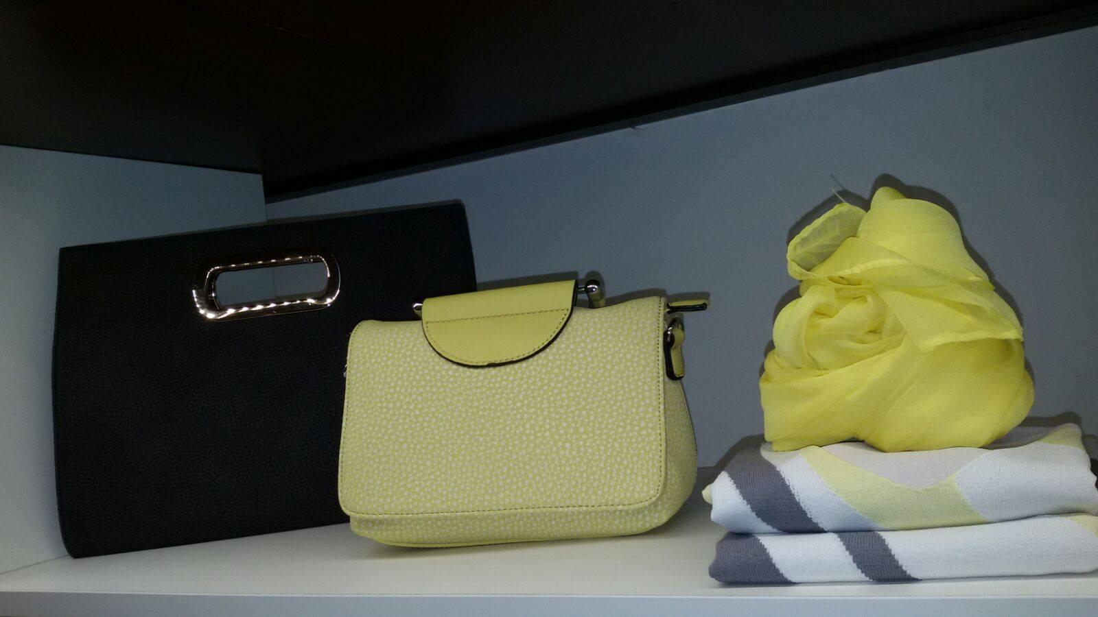 una mensola con delle borsette di color nero, giallo e delle sciarpe