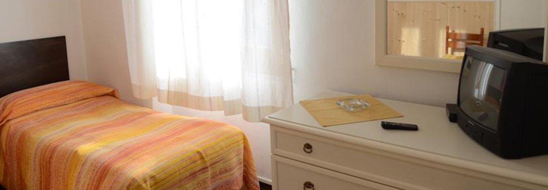 interno di una camera singola con mobile e televisore