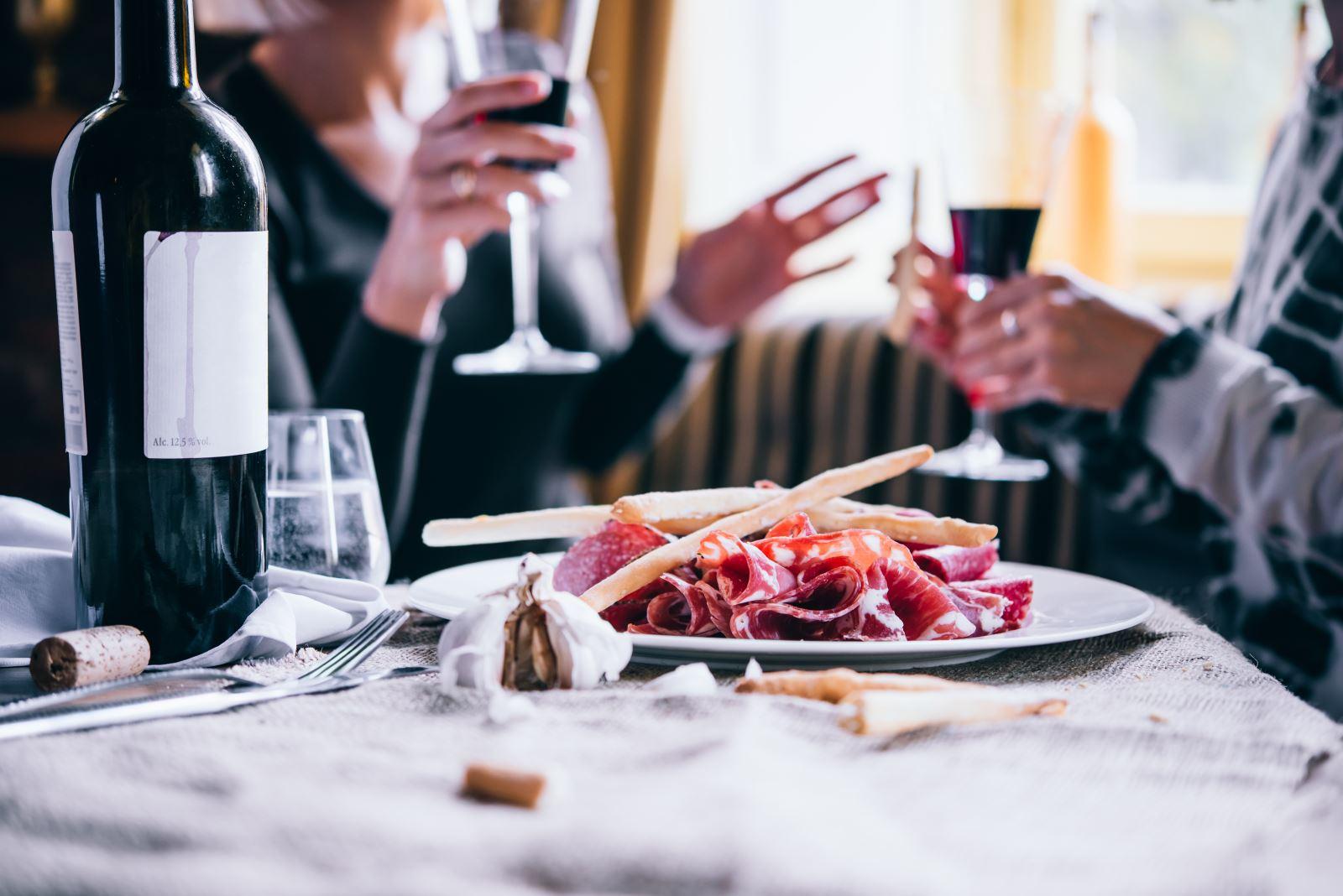 un piatto di affettati con due grissini e due persone con dei bicchieri di vino rosso