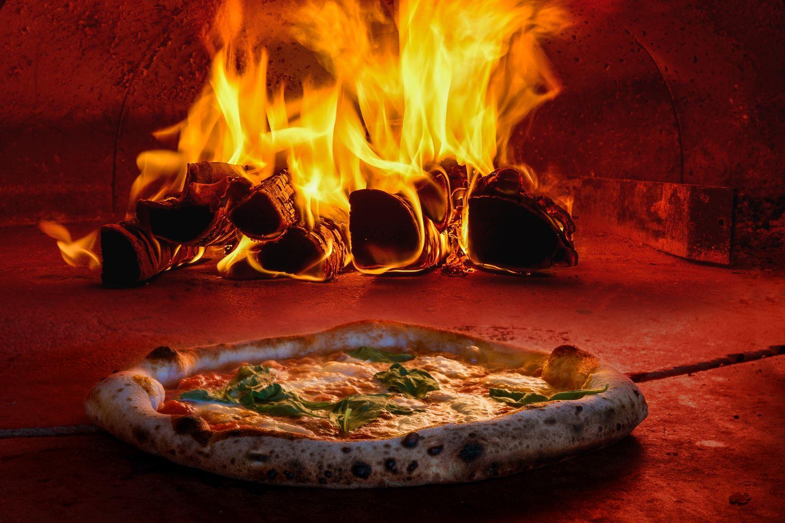 una pizza e delle legna che brucia in un forno