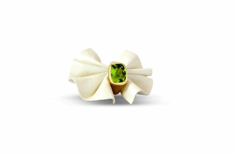un anello d'oro con una pietra verde e della stoffa bianca attorna a formare dei petali