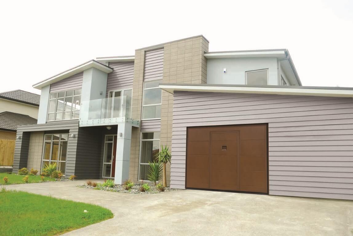 Abitazione con cancello marrone di garage in primo piano