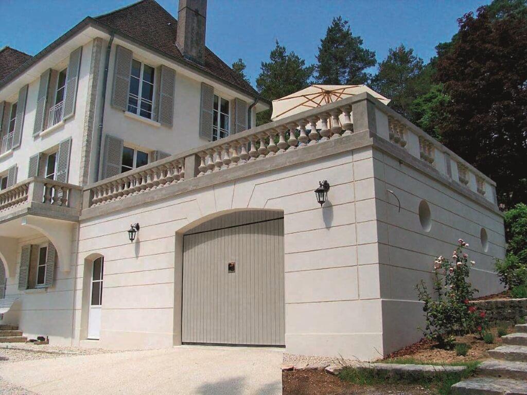 Casa in pietra grigia con porta di garage in primo piano
