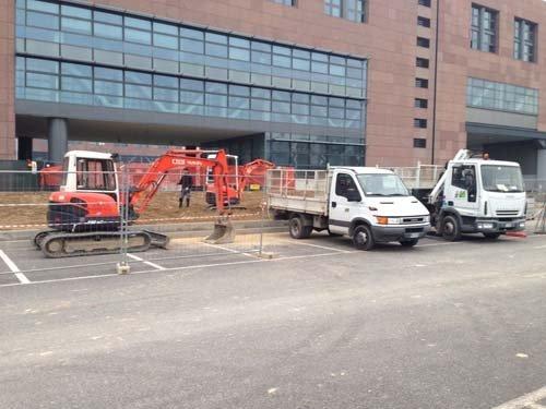 Furgoni e macchinari da giardinaggio parcheggiati all'esterno di uno stabilimento