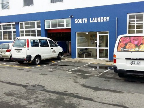 South Laundry front of business with vehicles parked outside