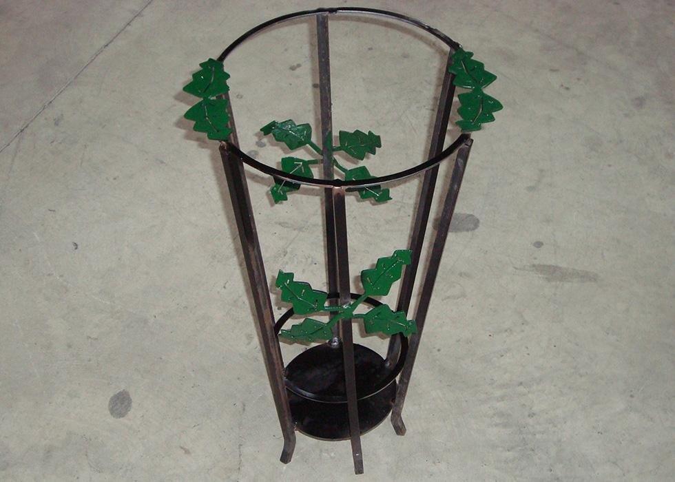 un porta vaso in ferro battuto con delle foglie verdi