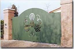 un cancello verde in ferro con dei disegni al centro