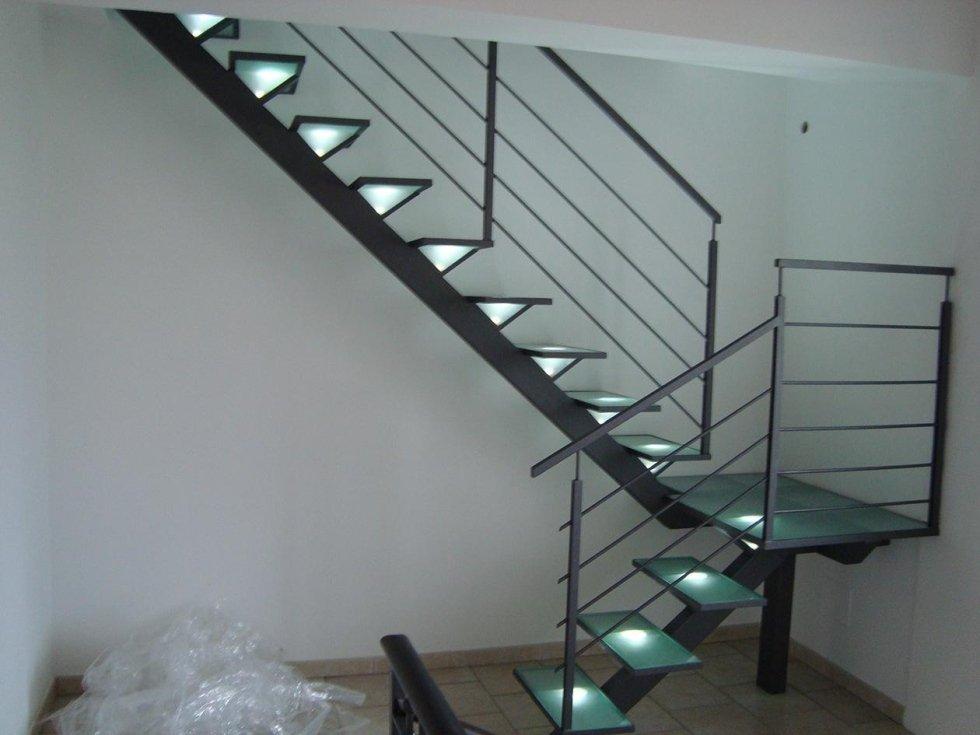 una scala con corrimano in ferro e gradini verdi