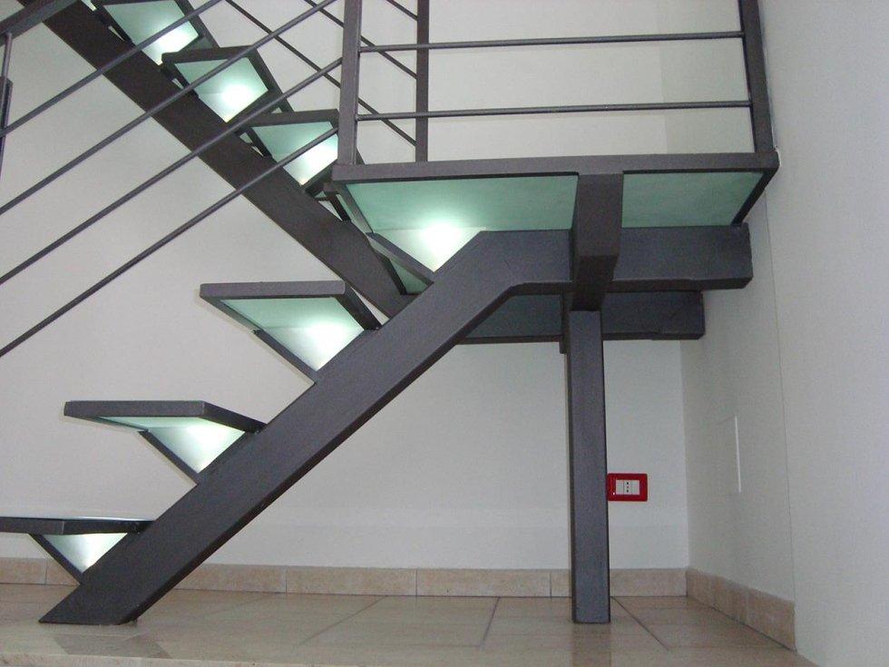 una scala con gradini in vetro e corrimano in ferro battuto