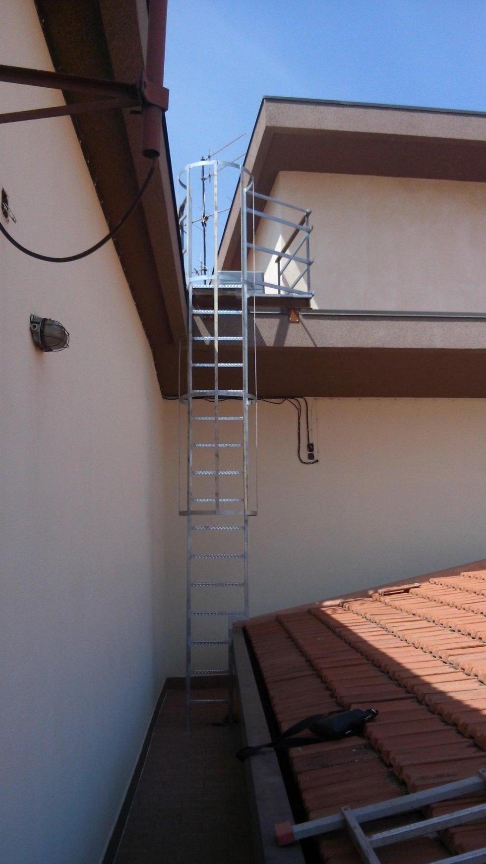 una scala grigia e sulla destra un tetto di una casa