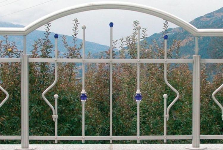 una ringhiera bianca, davanti delle piante e vista delle montagne