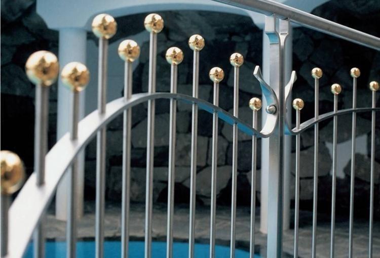 una ringhiera in ferro con delle finiture a palline dorate in cima
