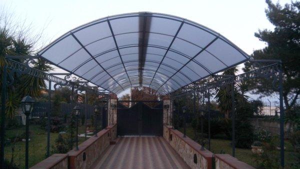 una lunga tettoia che conduce a un cancello d'entrata di una villa
