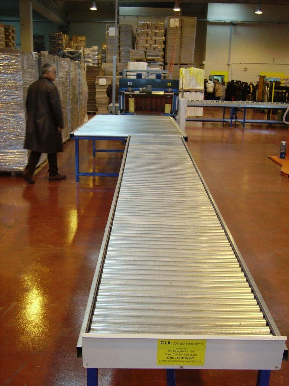 un nastro trasportatore a rulli in una fabbrica con vista dei bancali con del materiale e un uomo