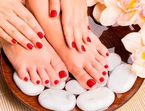 delle mani e dei piedi con dello smalto rosso