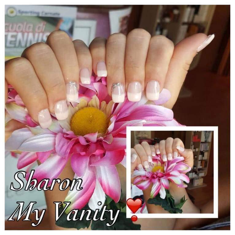 delle unghie di color bianco che tengono in mano un fiore bianco e fucsia e la scritta Sharon My Vanity