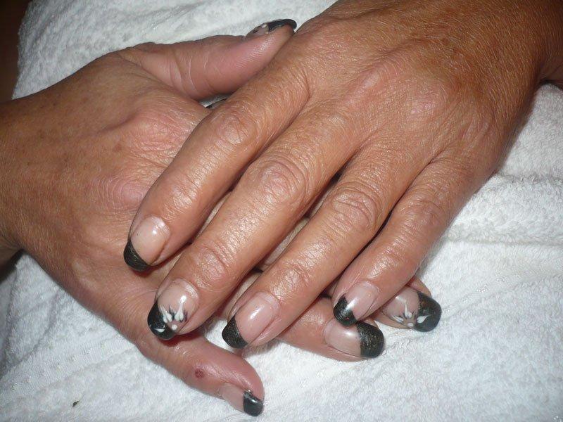 due mani con delle unghie nere e a disegni bianchi