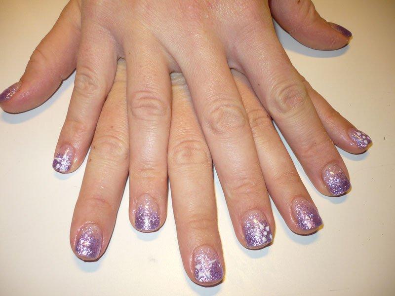delle mani con delle unghie viola a brillantini bianchi