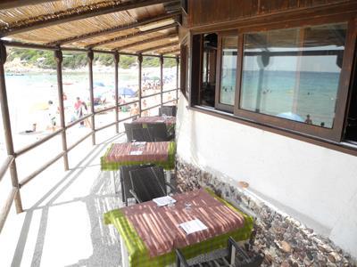 tavolini all`aperto sotto una tettoia fronte mare