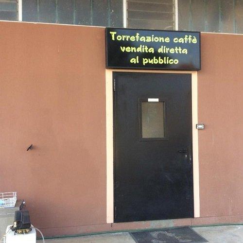 una porta d'ingresso e sopra la scritta Torrefazione caffe' vendita diretta al pubblico