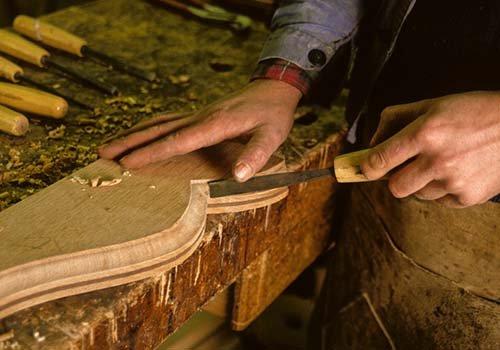 una mano con una lima e un'altra appoggiata su un asse di legno
