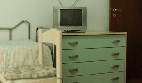 TiVu su la cassettiera verde e una sedia blanca accanto il letto