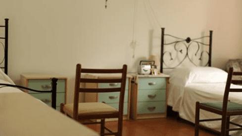Stanza con due letti, tre comodini e due sedie di legno