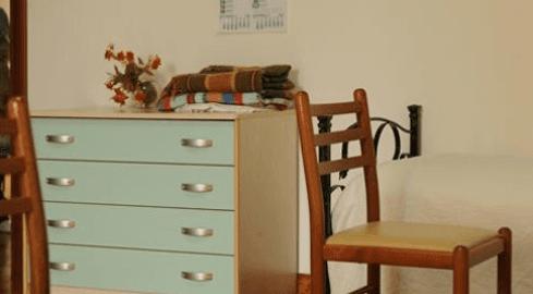 Sedia accanto il letto e una cassettiera verde con coperte sopra e un vasi di fiori