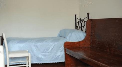 Banco di legno e sedia di legno bianca accanto il letto