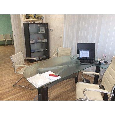 Interno dello studio medico con vista della sala di attesa, scrivania angolare di vetro, sedie di pelle in color crema