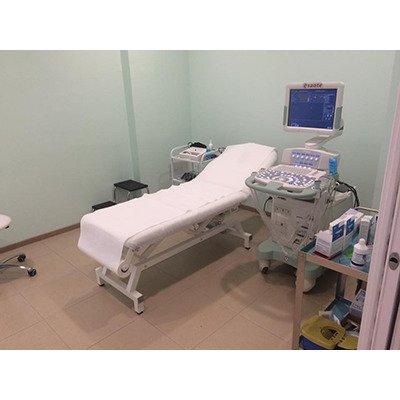 sala con lettino, carrello delle emergenze e macchianario di diagnosi con monitor