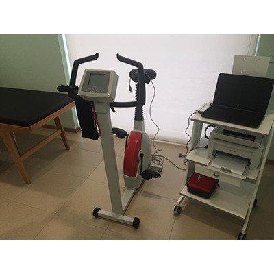 una cyclette e una piccola scrivania con computer portatile di color nero e sotto una stampante
