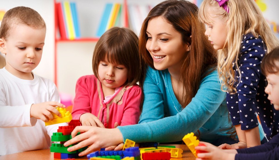 A nanny playing lego with children