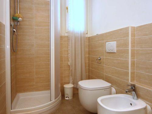 vista angolare di un bagno con box doccia, bide e parete in piastrelle